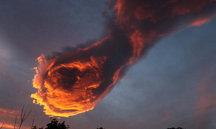 PIC FROM MERCURY PRESS (PICTURED: Cloud that looks like the 'hand of God')  These incredible photos appear to show that there is a fire power after all. A cloud that took the form of a 'hand of God' holding a fireball dominated the skyline above the north coast the Portuguese island of Madeira at around 8am on Monday (January 24). And weather blogger Rogerio Pacheco, 32, could not believe his luck when he looked up at the clouds while commuters made their way to work in the morning rush hour. The awe-inspiring snaps have since been shared online after Rogerio opted to post them on his blog. SEE MERCURY COPY